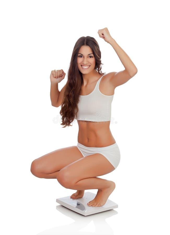 Donna felice che celebra il suo nuovo peso su una scala immagine stock