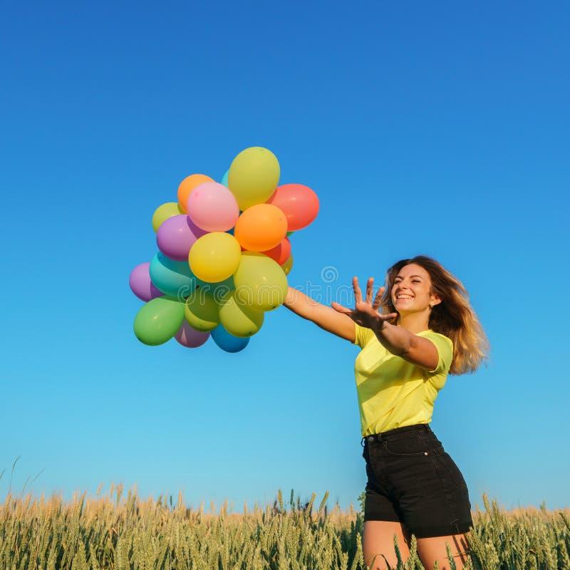 Donna felice che corre con un mazzo di palloni immagine stock