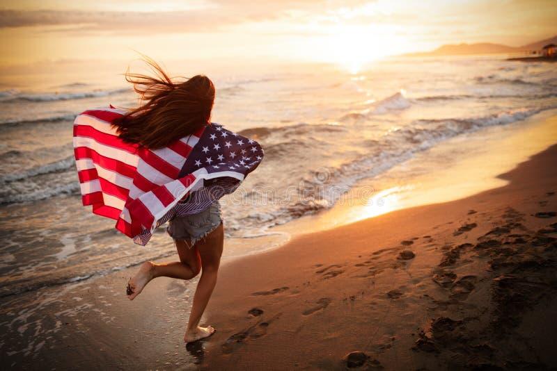 Donna felice che corre sulla spiaggia mentre celebrateing festa dell'indipendenza e godendo della libert? in U.S.A. immagini stock libere da diritti