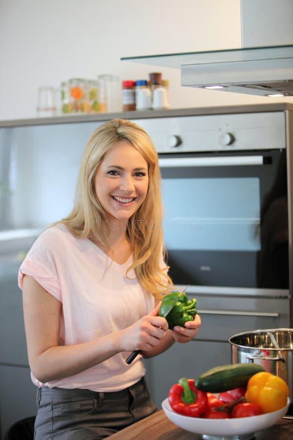 Donna felice che cucina un pasto nella cucina immagine stock