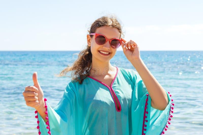Donna felice che dà i pollici sul segno della mano di successo fuori sulla spiaggia immagini stock