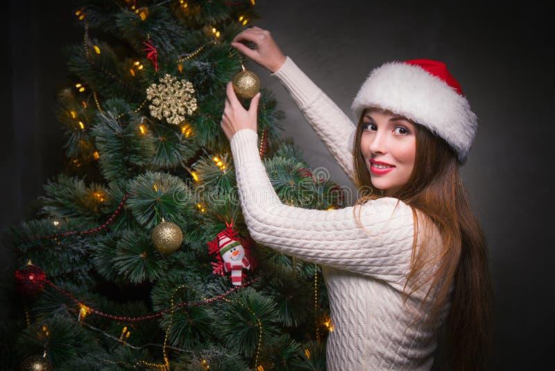 Donna felice che decora un albero di Natale fotografie stock libere da diritti