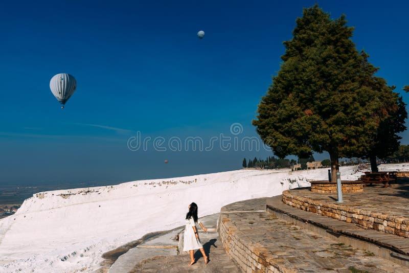 Donna felice che esamina i palloni nel cielo Bella ragazza in Turchia, Pamukkale Una donna esamina il cielo l'alba immagine stock