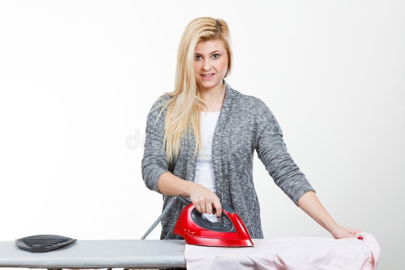 Donna felice che fa rivestire di ferro immagine stock