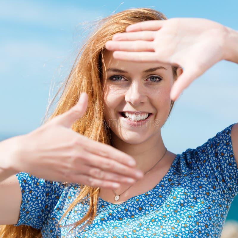 Donna felice che fa una struttura del dito fotografia stock