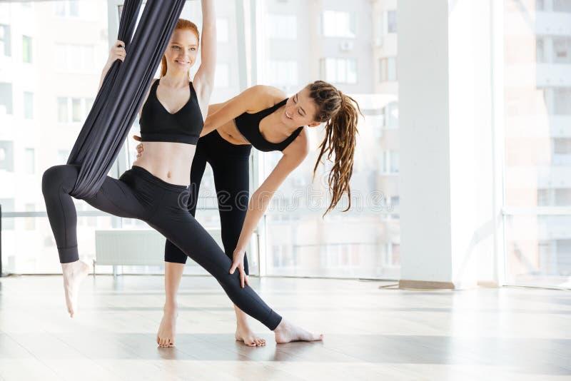 Donna felice che fa yoga aerea con l'istruttore in studio fotografie stock libere da diritti