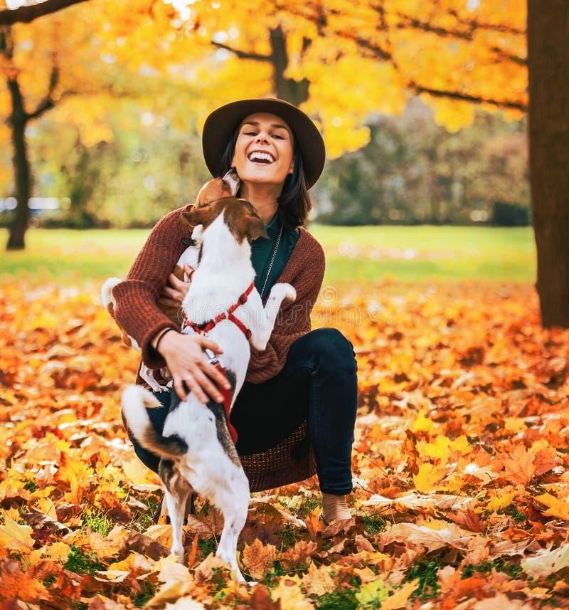 Donna felice che gioca con il cane all'aperto in autunno immagini stock libere da diritti