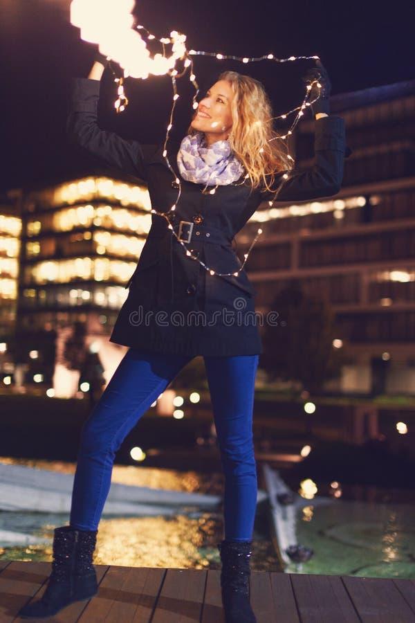 Donna felice che gioca con le luci leggiadramente di natale nella notte della città all'inverno fotografia stock libera da diritti