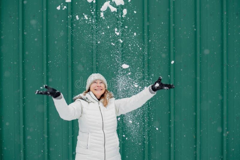 Donna felice che gioca nella neve fresca fotografia stock libera da diritti