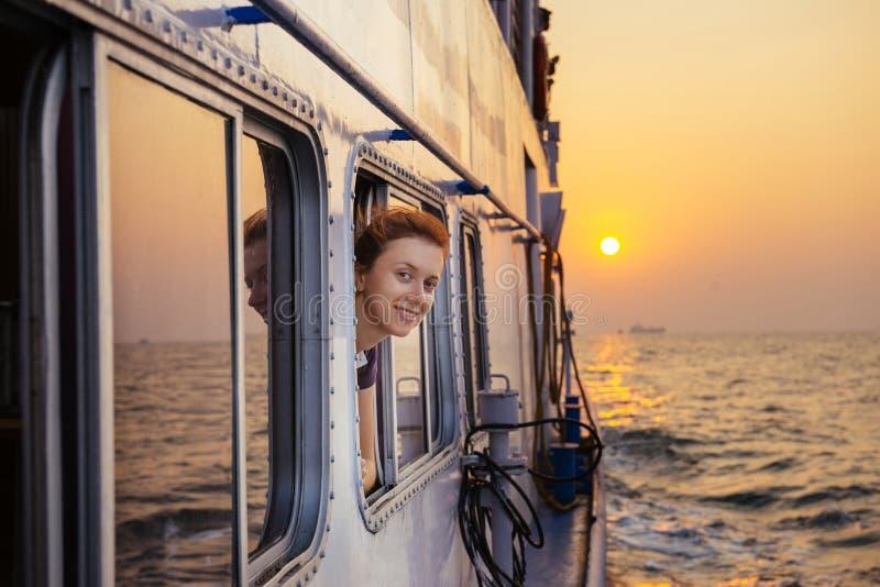 Donna felice che gode del mare dal traghetto sul tramonto immagini stock