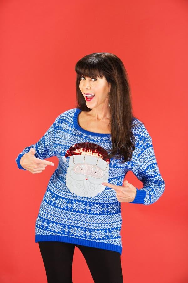 Donna felice che indica il suo maglione immagine stock