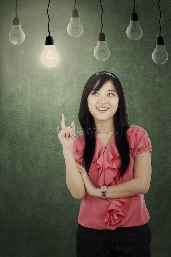 Donna felice che indica le lampade fotografie stock libere da diritti