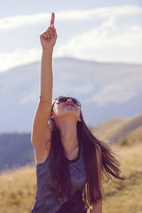 donna felice che indica verso il cielo fotografie stock