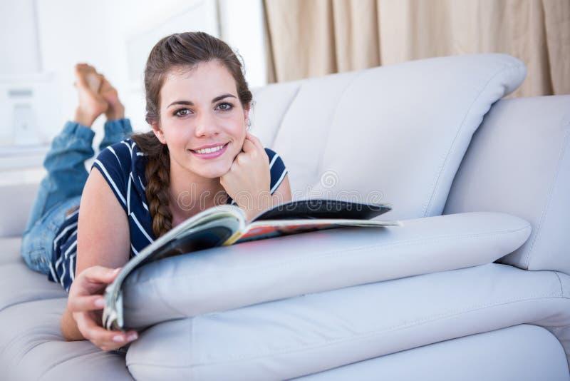 Donna felice che legge una rivista sullo strato fotografie stock