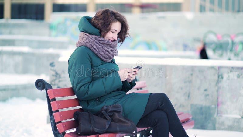 Donna felice che manda un sms su uno Smart Phone mentre sedendosi su un banco nella città di inverno contro i blocchi di pietra c immagine stock