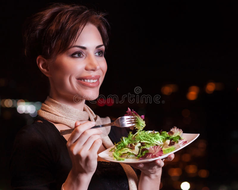 Donna felice che mangia insalata immagine stock