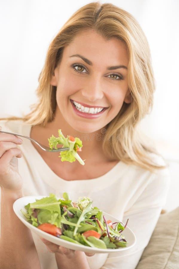Donna felice che mangia insalata di verdure fotografie stock libere da diritti