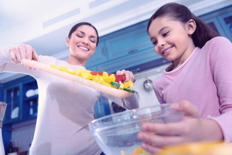 Donna felice che mette verdura nella ciotola dopo il taglio loro immagine stock