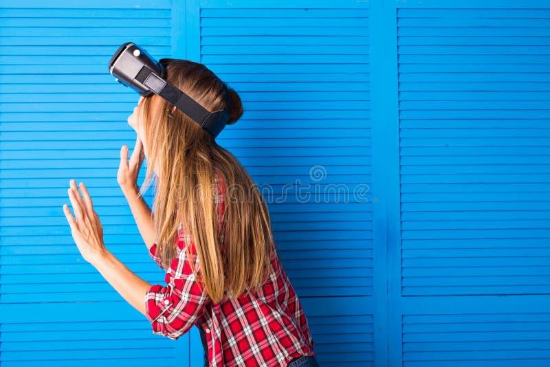 Donna felice che ottiene ad esperienza facendo uso dei vetri della VR-cuffia avricolare di realtà virtuale molte le mani gesticol immagine stock libera da diritti