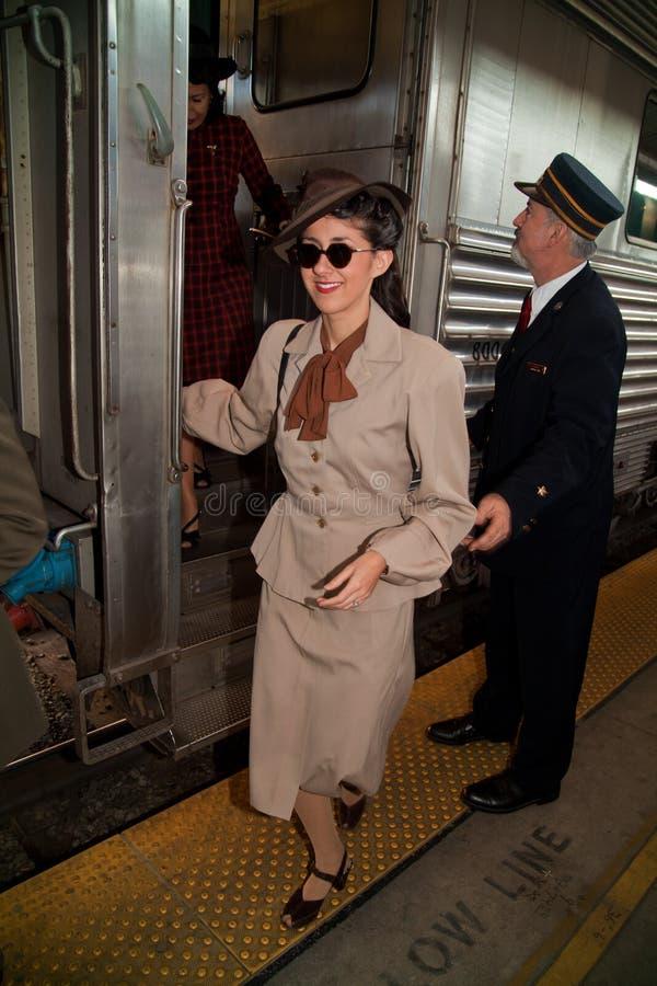 Donna felice che ottiene fuori treno fotografia stock