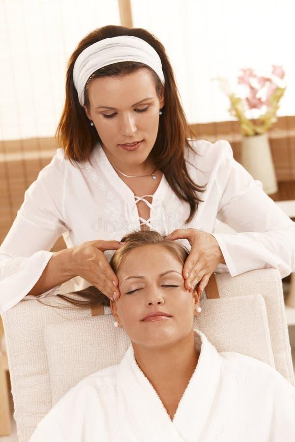Donna felice che ottiene massaggio capo fotografia stock