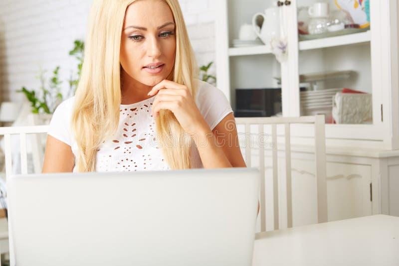 Donna felice che per mezzo del computer portatile immagine stock