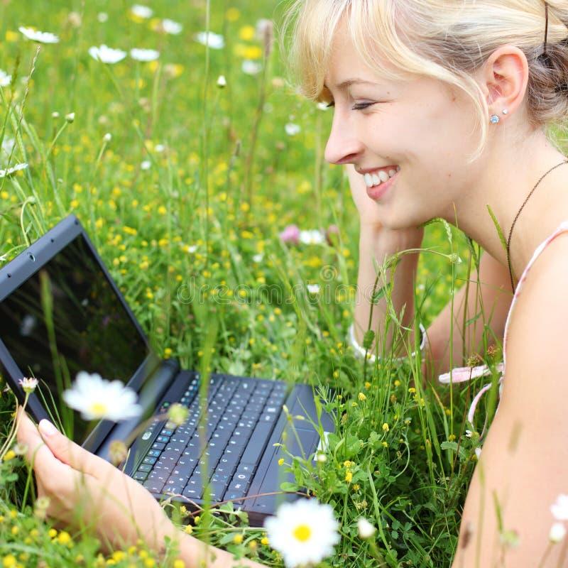 Donna felice che per mezzo del suo taccuino all'aperto fotografia stock