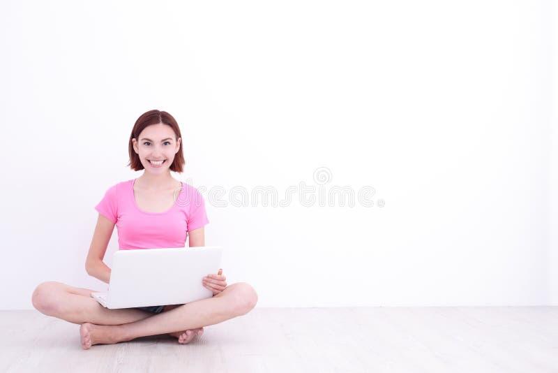 Donna felice che per mezzo della compressa digitale immagine stock