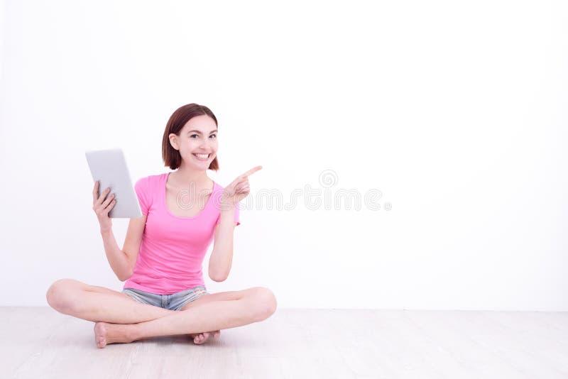 Donna felice che per mezzo della compressa digitale fotografia stock