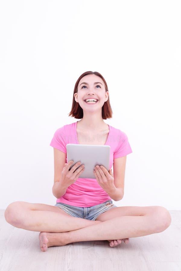 Donna felice che per mezzo della compressa digitale immagine stock libera da diritti