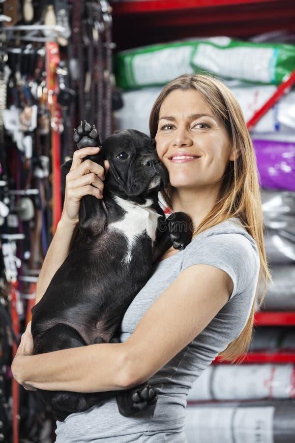 Donna felice che porta bulldog francese al deposito dell'animale domestico fotografia stock libera da diritti