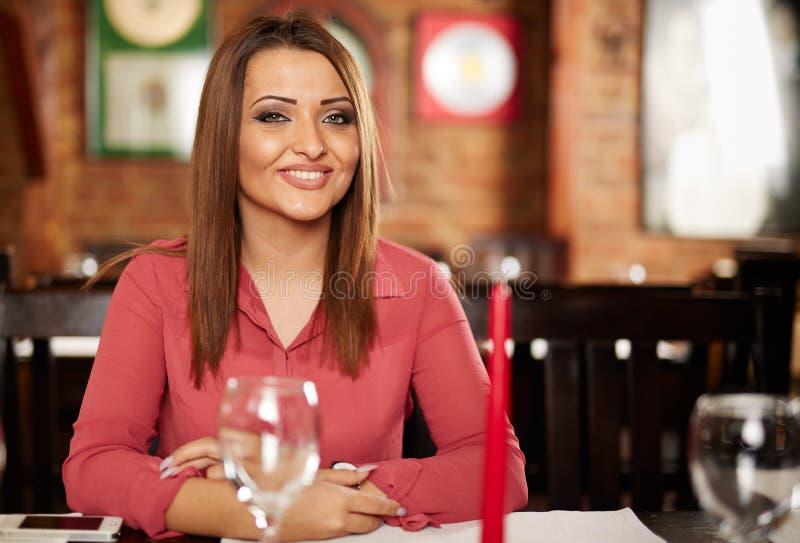 Donna felice che posa in un ristorante fotografie stock libere da diritti