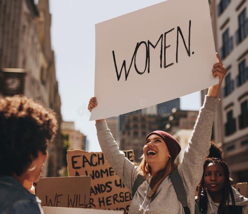 Donna felice che protesta con il segno scritto mano fotografia stock