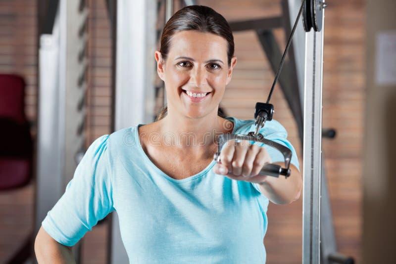 Donna felice che risolve nel club di salute immagini stock