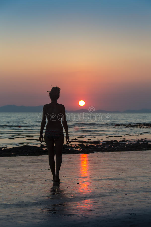 Donna felice che salta nel tramonto del mare fotografia stock