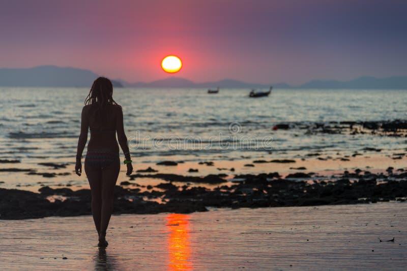 Donna felice che salta nel tramonto del mare immagini stock libere da diritti