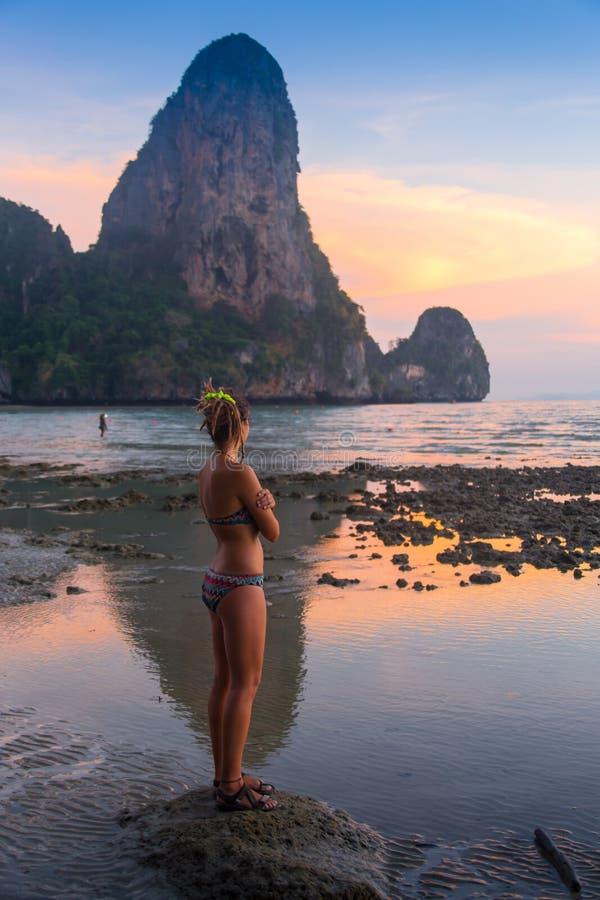Donna felice che salta nel tramonto del mare immagine stock libera da diritti