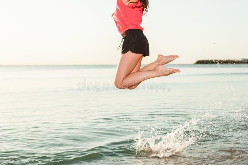 Donna felice che salta in primo piano di alba del mare fotografie stock libere da diritti