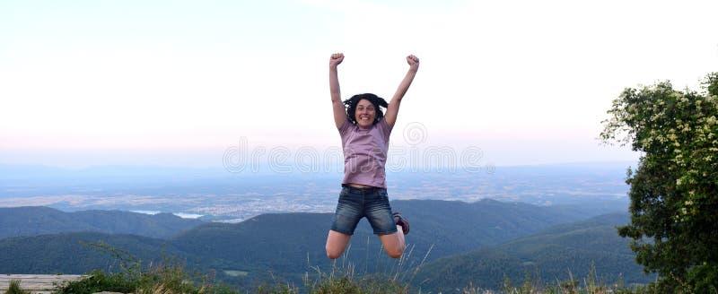 Donna felice che salta quando ha raggiunto la cima immagini stock