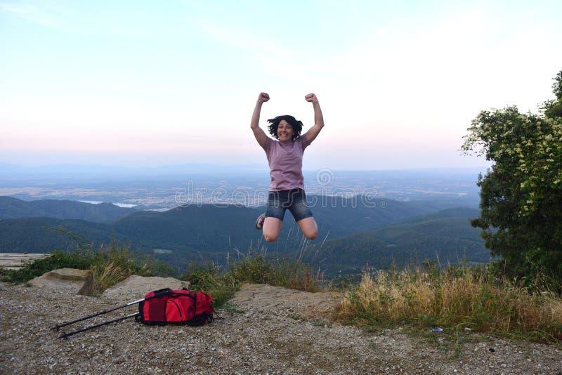 Donna felice che salta quando ha raggiunto la cima immagine stock libera da diritti
