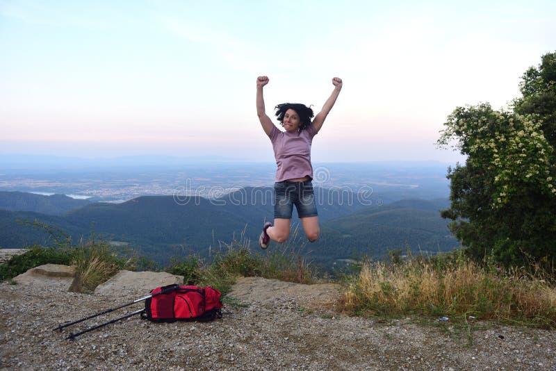Donna felice che salta quando ha raggiunto la cima fotografia stock