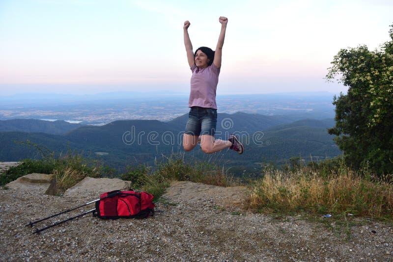 Donna felice che salta quando ha raggiunto la cima immagine stock