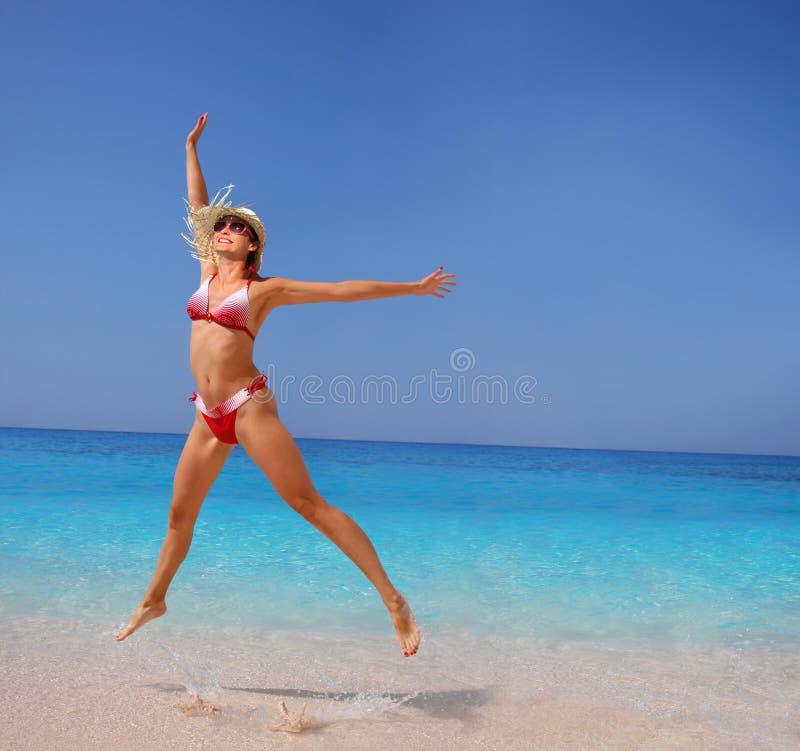 Donna felice che salta sulla spiaggia immagine stock libera da diritti