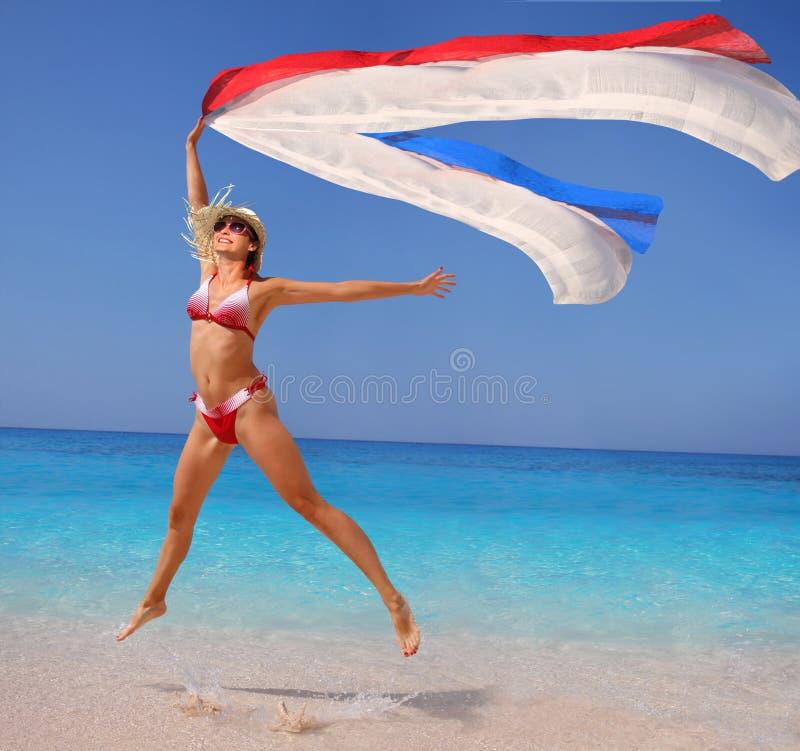 Donna felice che salta sulla spiaggia fotografie stock