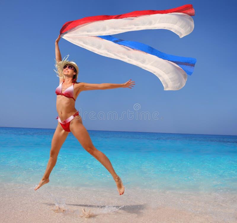 Donna felice che salta sulla spiaggia fotografie stock libere da diritti