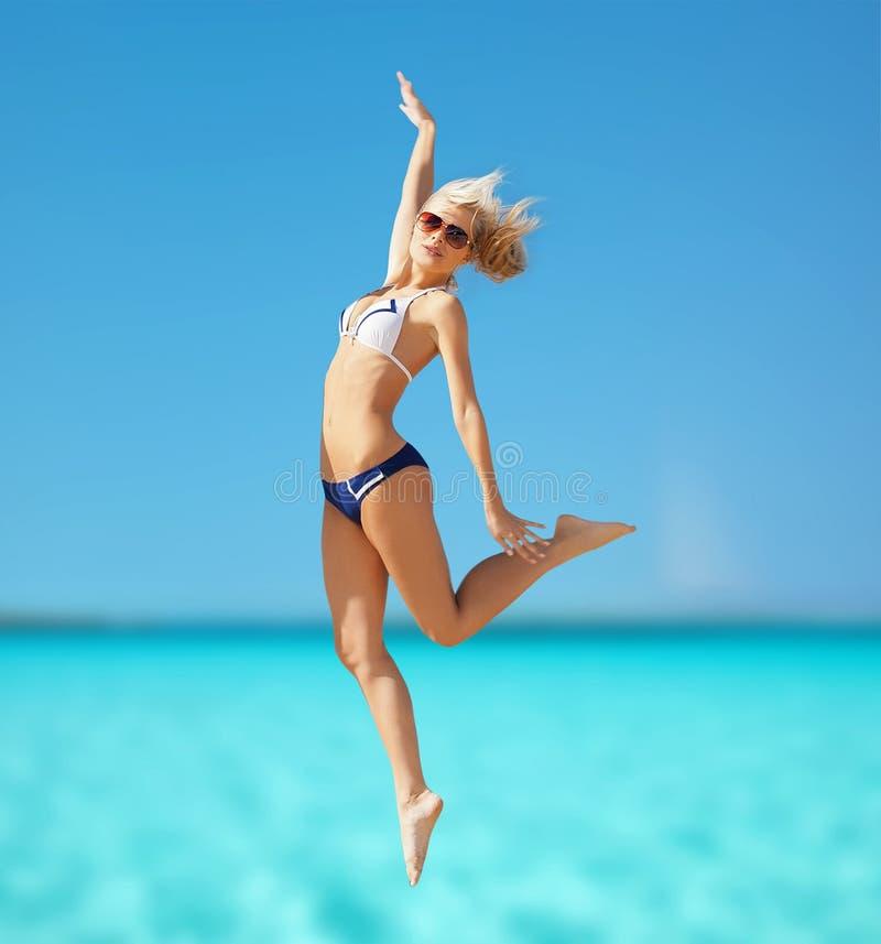 Donna felice che salta sulla spiaggia fotografia stock libera da diritti