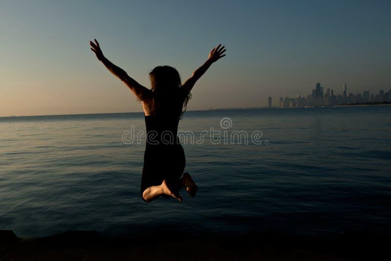 Donna felice che salta vicino dal lago Michigan all'alba fotografie stock libere da diritti