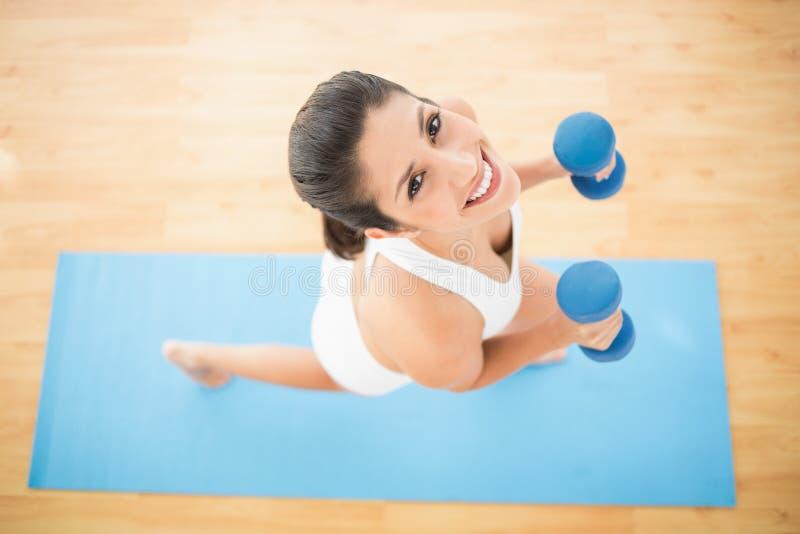 Donna felice che si esercita con le teste di legno sulla stuoia blu di esercizio immagine stock