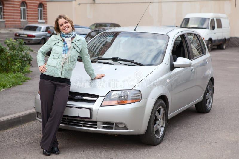 Donna felice che si leva in piedi davanti alla propria automobile fotografia stock