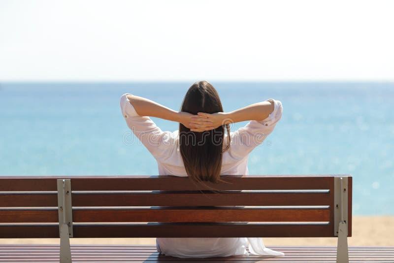 Donna felice che si rilassa contemplando oceano sulla spiaggia fotografia stock